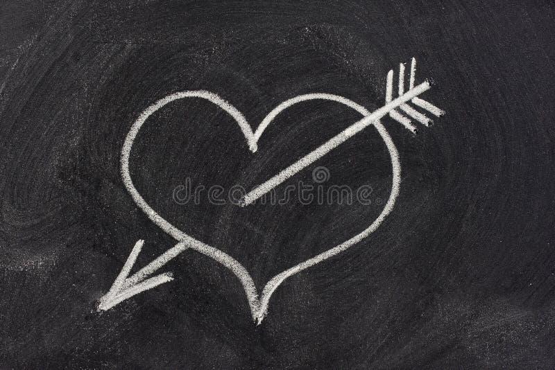 Corazón perforado por la flecha, símbolo del amor en la pizarra fotos de archivo