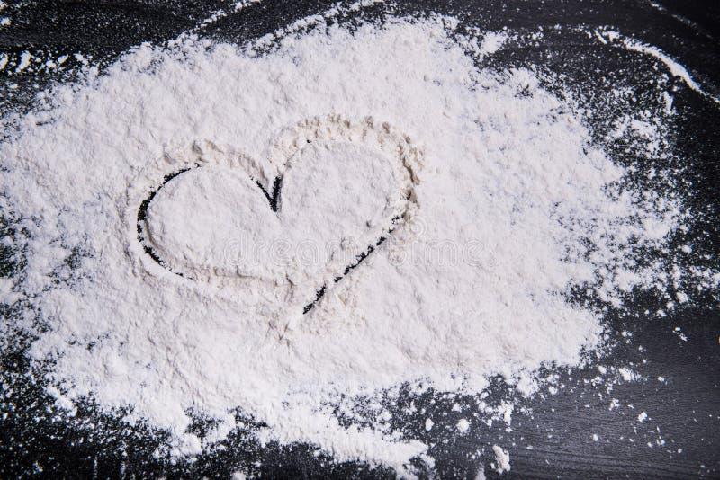 Corazón pintado con el finger en comida del trigo en una superficie de funcionamiento gris foto de archivo