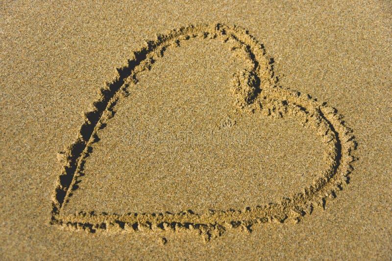 Corazón precioso en arena en la playa imagen de archivo