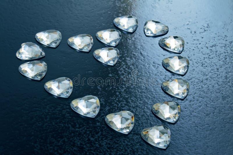 Corazón presentado de pequeños corazones cristalinos en un fondo azul foto de archivo