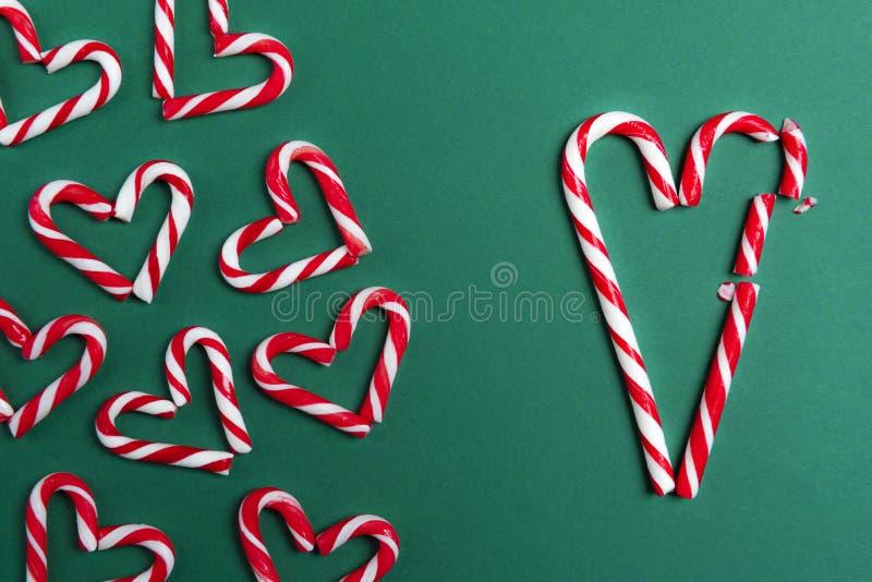 Corazón quebrado grande de los bastones de caramelo y pequeños corazones imagenes de archivo