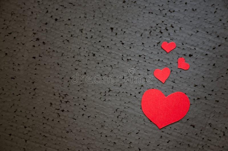 Corazón rojo brillante hermoso en un fondo negro áspero Un símbolo del amor y del fondo del día de tarjetas del día de San Valent foto de archivo
