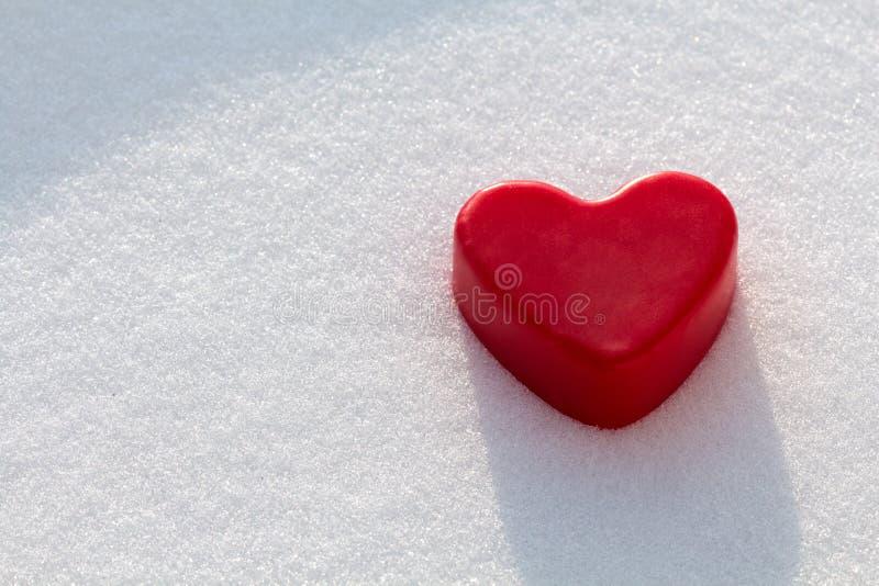 Corazón rojo de la cera en la nieve imagenes de archivo