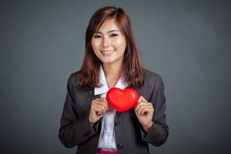 Corazón rojo de la demostración asiática feliz de la empresaria en su pecho fotografía de archivo