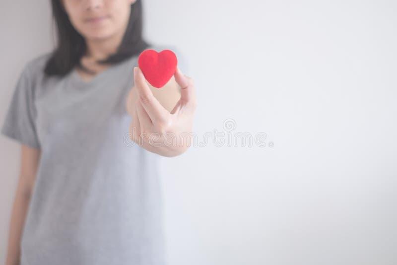 Corazón rojo de la demostración asiática hermosa de la mujer aislado en un fondo blanco con el espacio de la copia foto de archivo