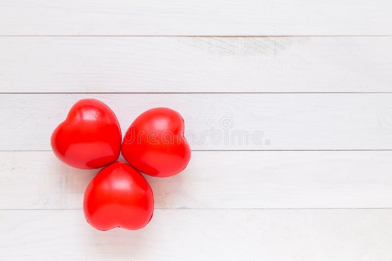 Corazón rojo de la visión superior en el tablón de madera blanco Para el amor o la tarjeta del día de San Valentín imagenes de archivo