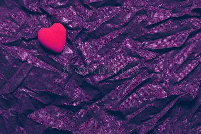 Corazón rojo de la visión superior en fondo púrpura oscuro arrugado de la textura El día de tarjeta del día de San Valentín y con foto de archivo