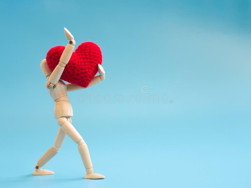 Corazón rojo de madera el caminar y del control de la marioneta en el fondo de pantalla de azul de cielo Manija de madera de la m fotografía de archivo