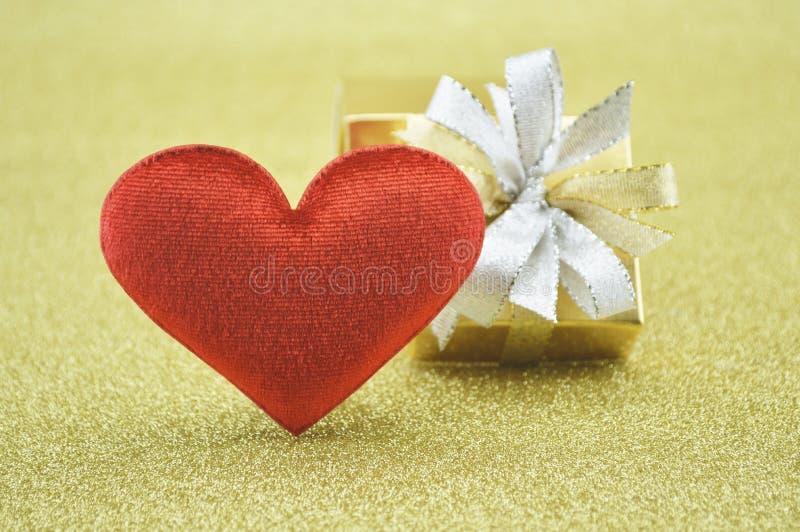 Corazón rojo del amor de la tela con la caja de regalo en el fondo del oro, estafa del amor fotos de archivo libres de regalías