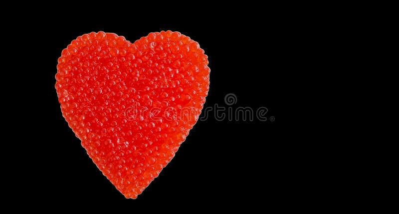 Corazón rojo del caviar aislado en negro imagenes de archivo