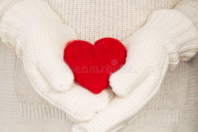 Corazón rojo del día de tarjetas del día de San Valentín en manos con las manoplas fotos de archivo