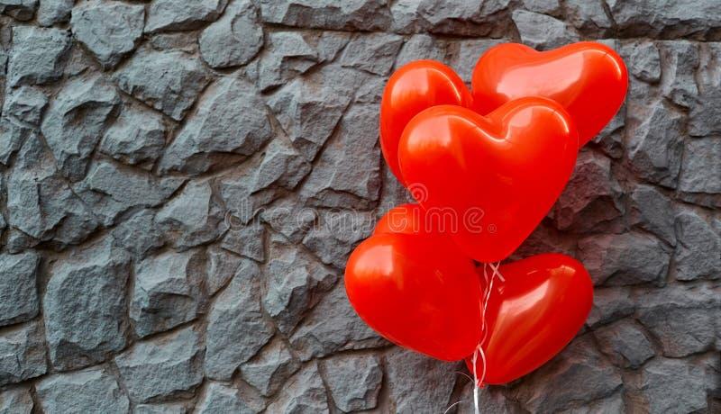 Corazón rojo del globo en un fondo de la piedra gris foto de archivo libre de regalías