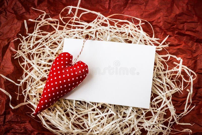 Corazón rojo del juguete y tarjeta en blanco en la paja fotos de archivo libres de regalías
