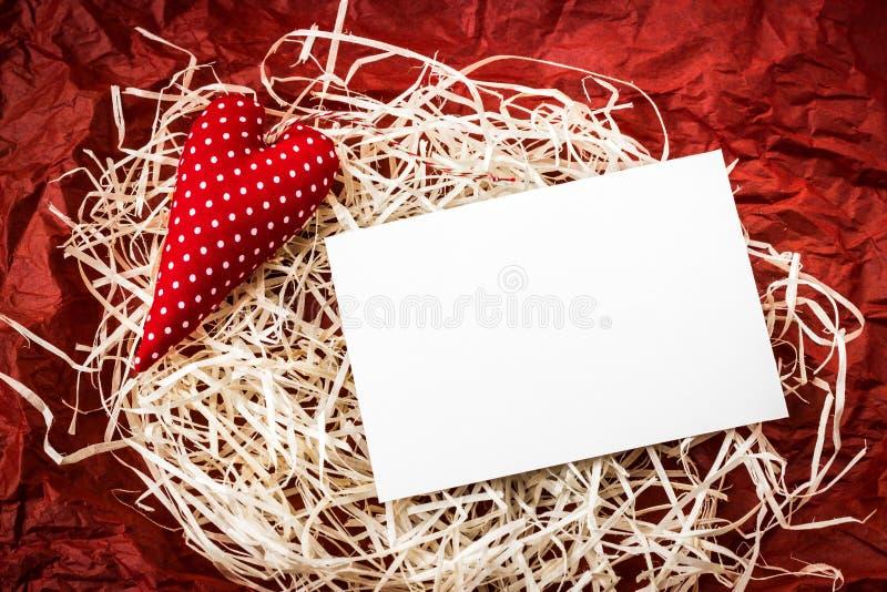 Corazón rojo del juguete y tarjeta en blanco en la paja imagen de archivo libre de regalías