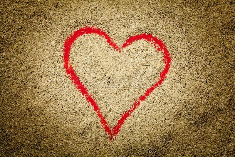 Corazón rojo dibujado en la arena imágenes de archivo libres de regalías
