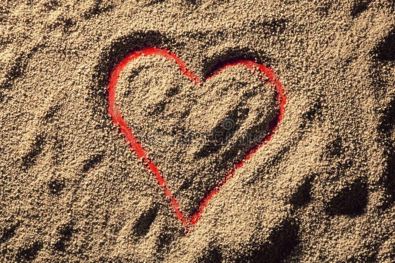 Corazón rojo dibujado en la arena fotografía de archivo