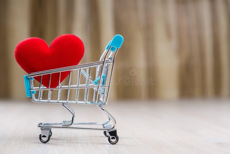 Corazón rojo en el carro de la compra imagen de archivo