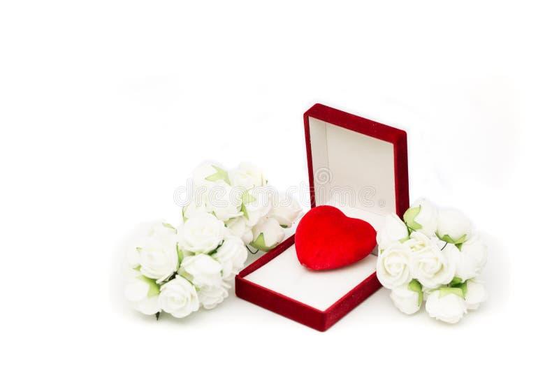 Corazón rojo en el joyero rojo con las decoraciones de la rosa del blanco foto de archivo libre de regalías