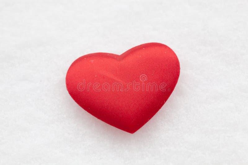 Corazón rojo en la nieve fotos de archivo