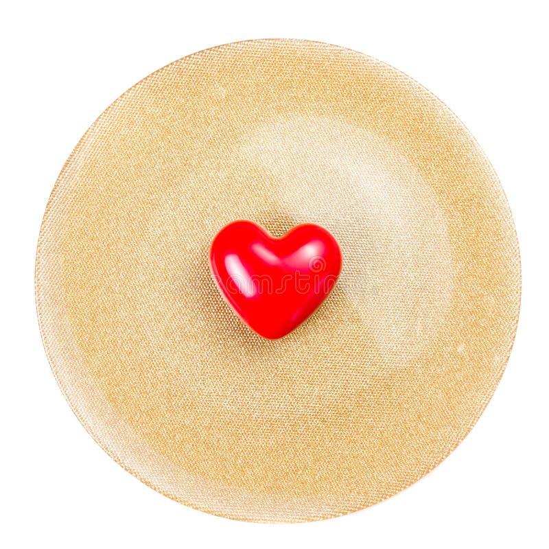 Corazón rojo en la placa de oro festiva aislada en el backgroun blanco imagen de archivo libre de regalías