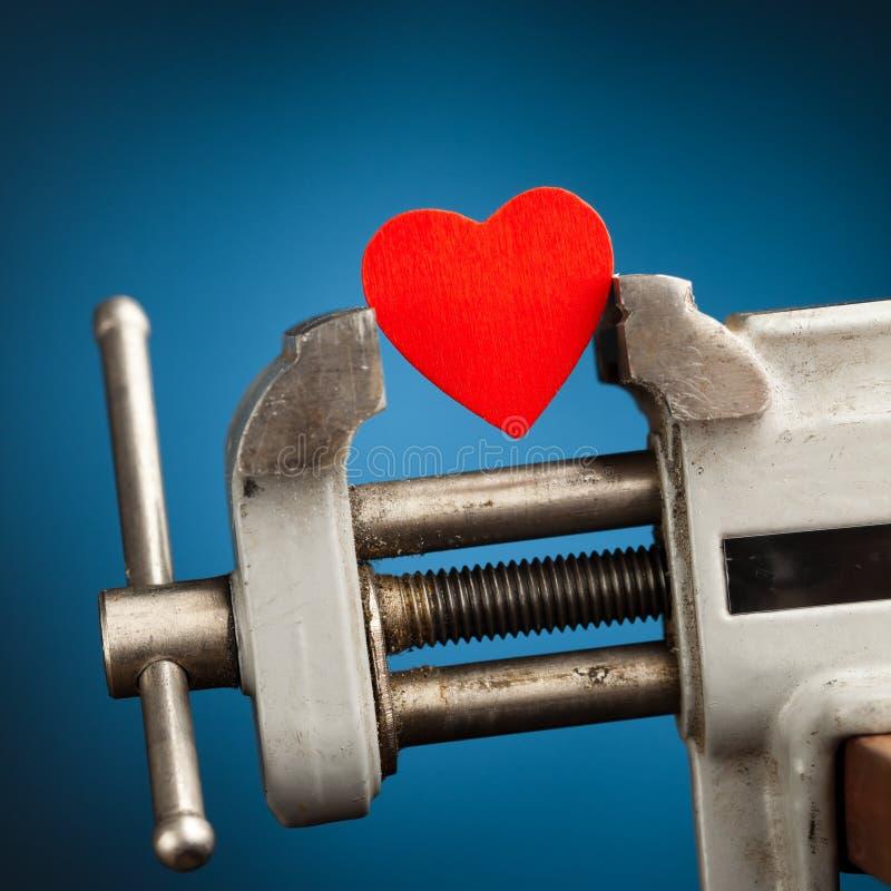 Corazón rojo en la vice herramienta imagen de archivo