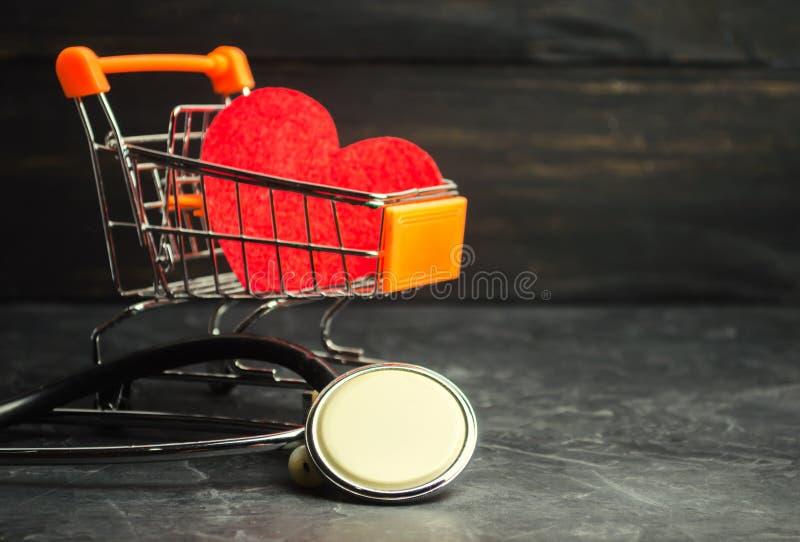 Corazón rojo en una carretilla y un estetoscopio del supermercado El concepto de medicina y de seguro médico, familia, vida ambul fotos de archivo