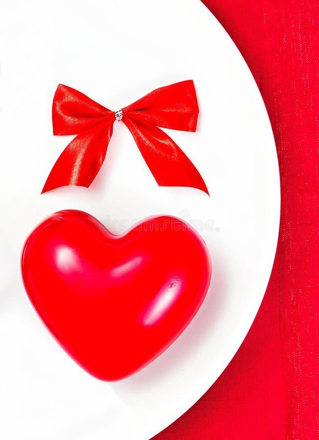 Corazón rojo en una placa blanca de la placa en servilleta festiva con el arco rojo. imágenes de archivo libres de regalías