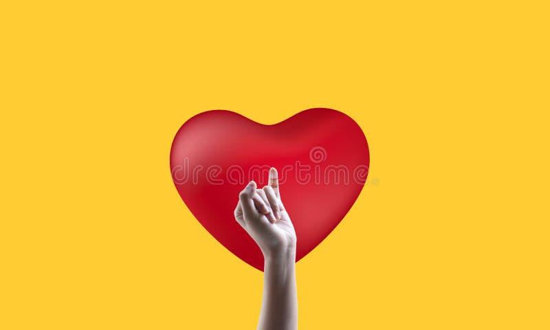 Corazón rojo, fondo amarillo y la mano de la mujer hermosa imagen de archivo libre de regalías