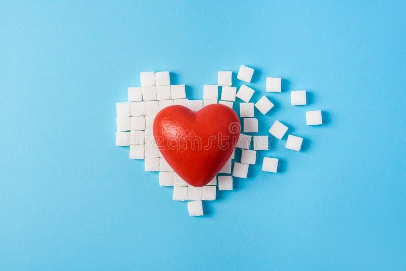 Corazón rojo grande en el corazón quebrado hecho de los cubos del azúcar en un fondo azul imagen de archivo