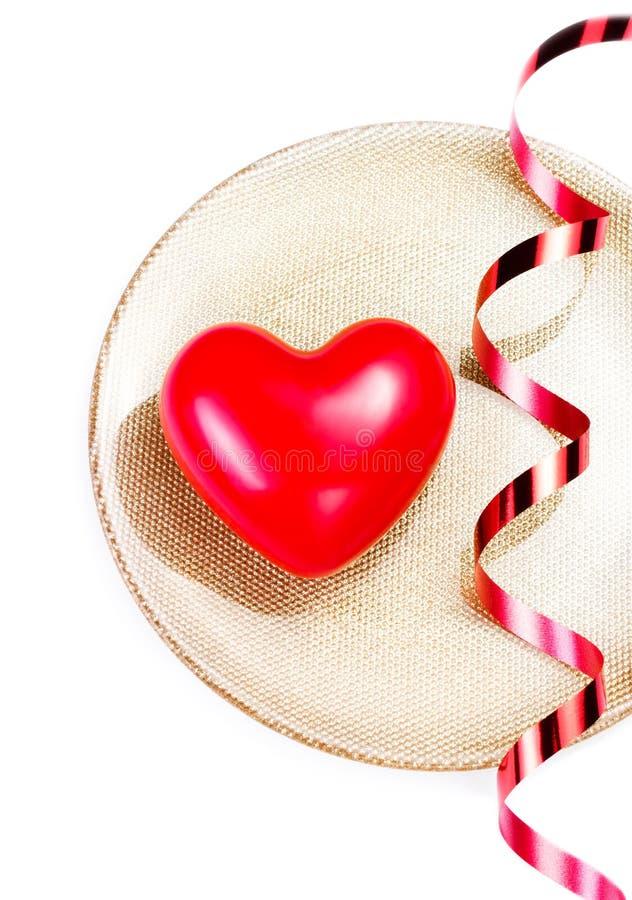 Corazón rojo grande en una placa de oro aislada en blanco con r festivo imagen de archivo libre de regalías