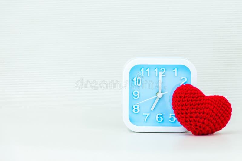 Corazón rojo hecho a mano que hace punto con el reloj Día del ` s de la tarjeta del día de San Valentín o concepto del amor fotografía de archivo