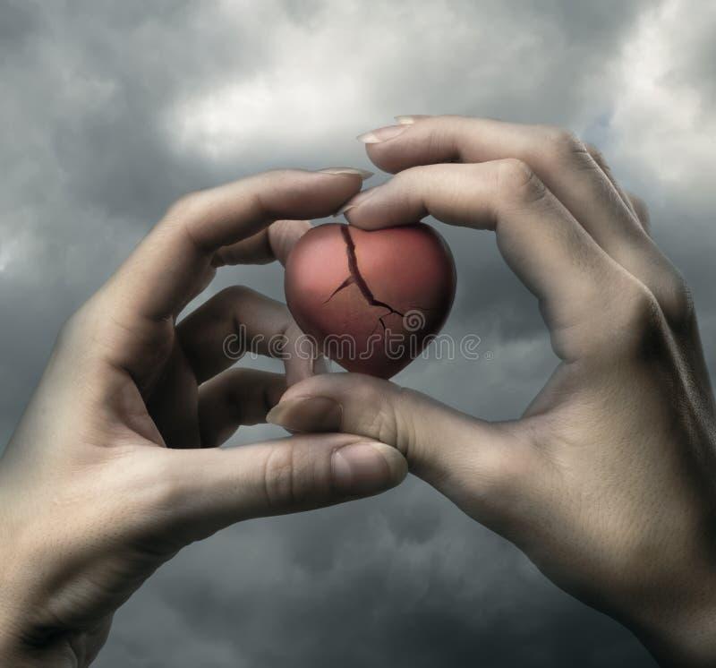 Corazón rojo quebrado en manos foto de archivo libre de regalías