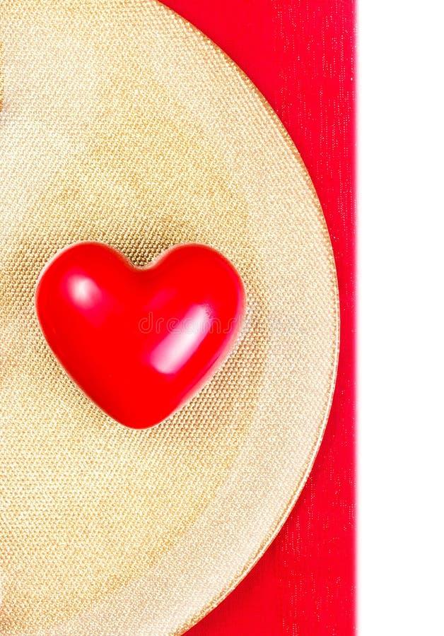 Corazón rojo sobre la placa de oro en el mantel rojo aislado en blanco foto de archivo libre de regalías