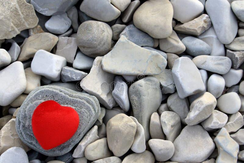 Corazón rojo sobre una piedra imaginada. muchas piedras grises foto de archivo