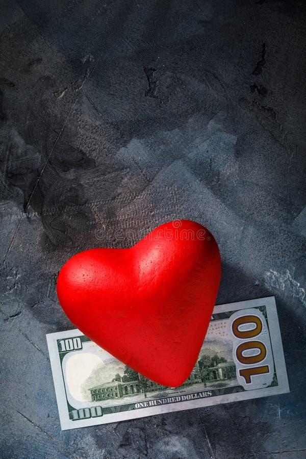 Corazón rojo y cientos dólares en la tabla con el espacio de la copia Concepto en el tema del amor para el dinero imagenes de archivo