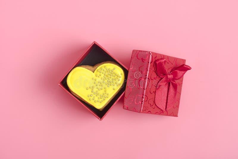 Corazón romántico amarillo del pan de jengibre en una caja de regalo roja en un fondo rosado de moda imágenes de archivo libres de regalías