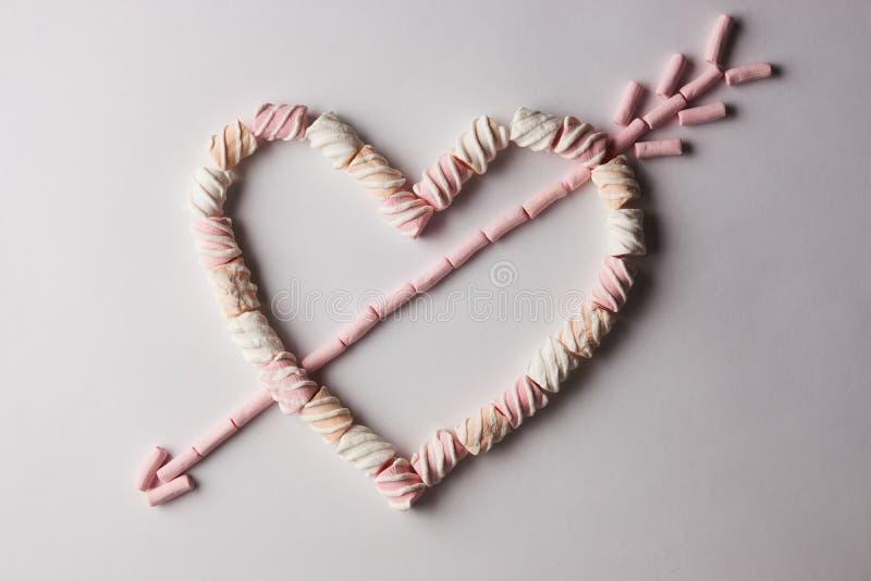 Corazón romántico con la flecha hecha de la melcocha fotografía de archivo