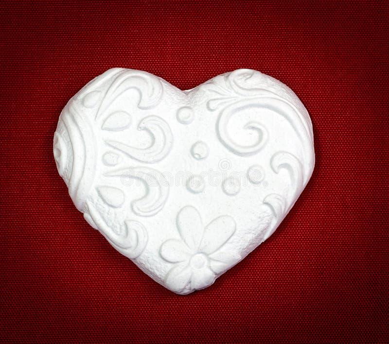 Corazón romántico en fondo rojo imagen de archivo