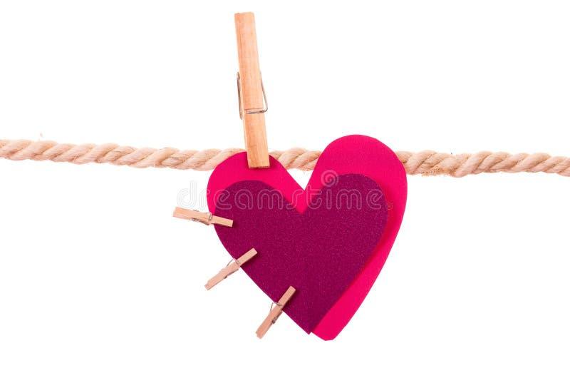 Corazón rosado con la ejecución atada pequeñas pinzas imagen de archivo libre de regalías