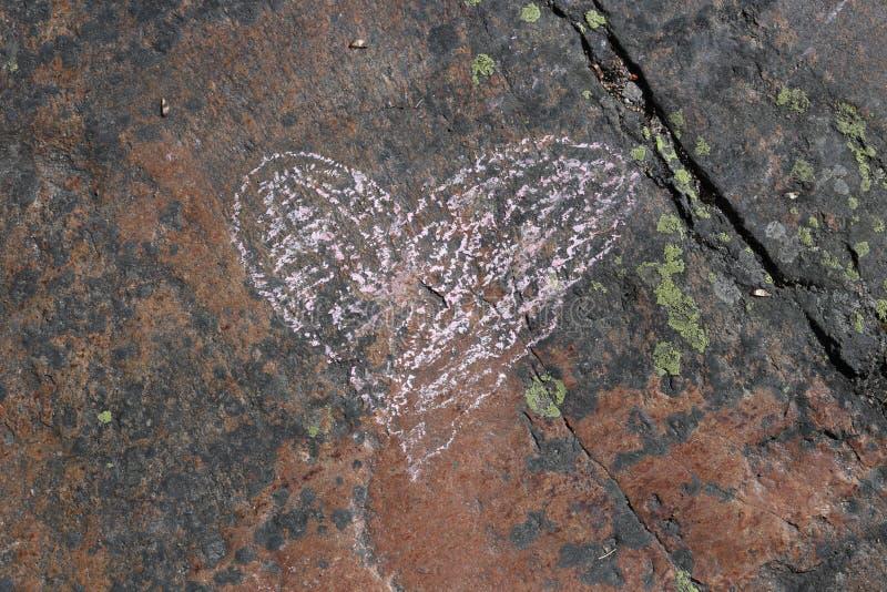 Corazón rosado dibujado en una superficie roja de la roca imagen de archivo libre de regalías