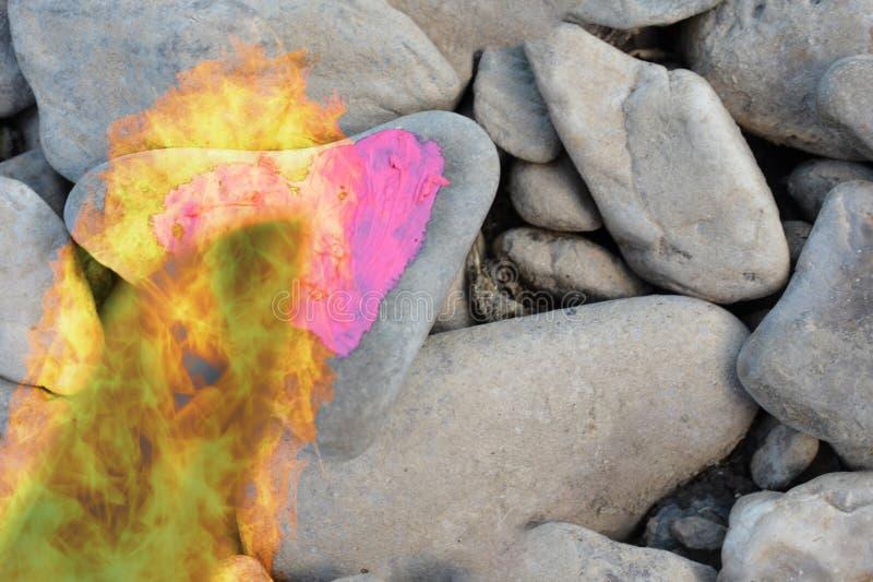 Corazón rosado que se zambulle del fuego del corte pintado con el lápiz labial en el pedazo de piedra imágenes de archivo libres de regalías