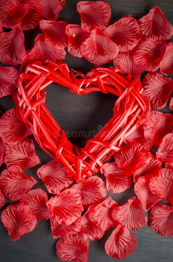 Corazón trenzado hermoso y pétalos color de rosa fotos de archivo libres de regalías