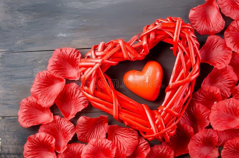 Corazón trenzado hermoso y pétalos color de rosa imagen de archivo