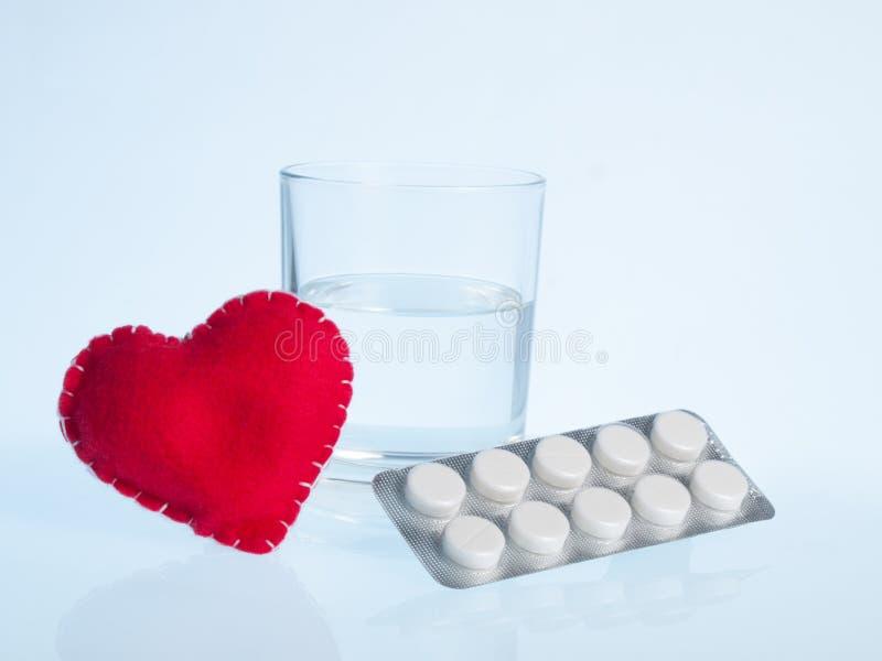 Corazón, vidrio de agua y píldoras foto de archivo libre de regalías