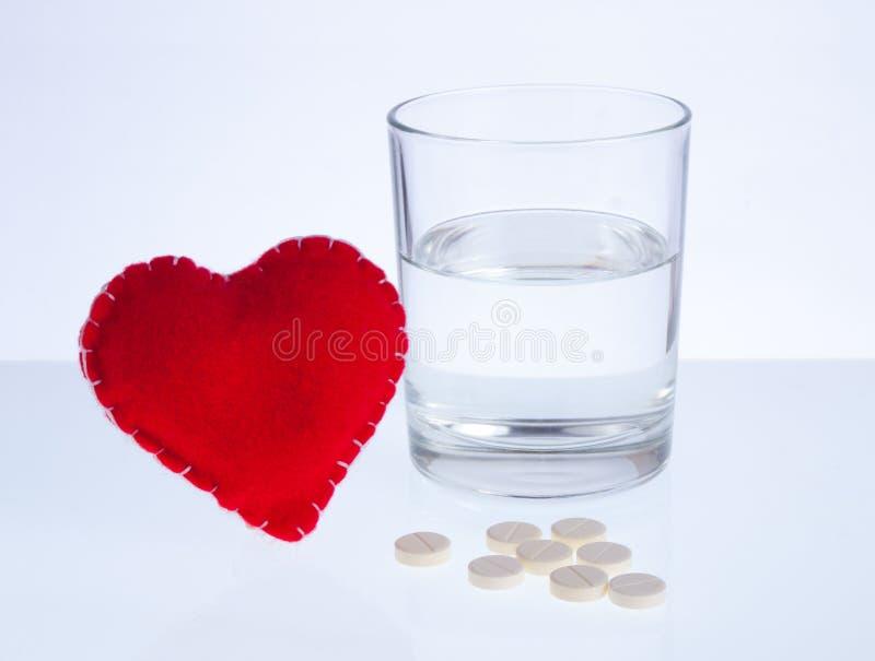 Corazón, vidrio de agua y píldoras imagen de archivo