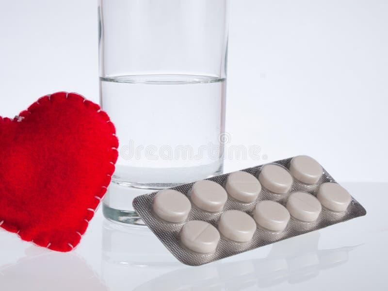 Corazón, vidrio de agua y píldoras fotos de archivo libres de regalías
