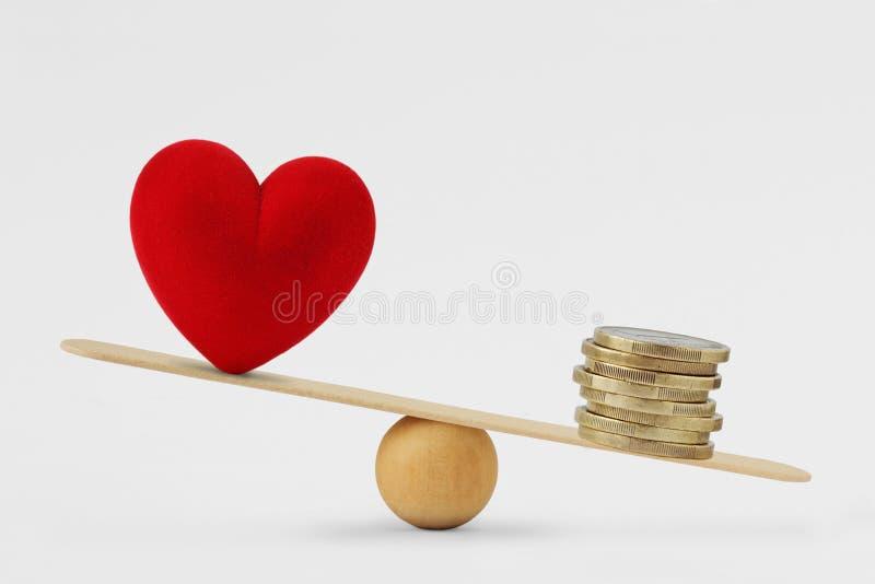 Corazón y dinero en la escala de la balanza - concepto de prioridad del dinero en vida imagen de archivo libre de regalías