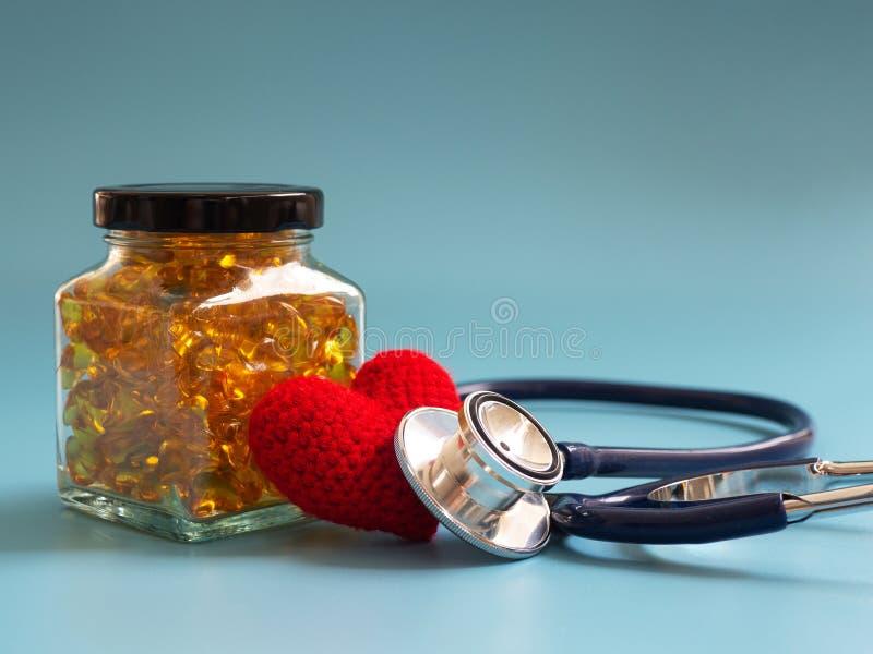 Corazón y estetoscopio rojos al lado de cápsulas del aceite de pescado en las botellas de cristal en fondo azul Omega-3 sano y es foto de archivo