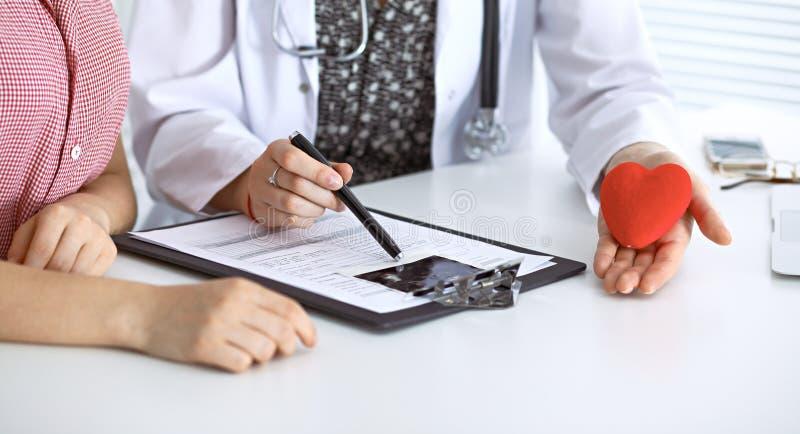 Corazón y paciente del doctor Médico que discute el examen de la salud con la madre futura Medicina, atención sanitaria y embaraz foto de archivo