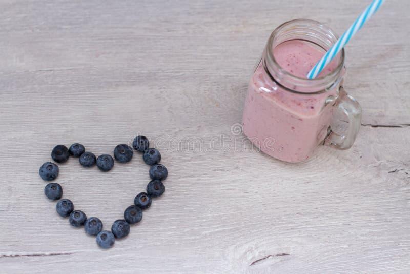 Corazón y smoothie de la forma de Blueberrie en una taza del tarro con una paja imagenes de archivo